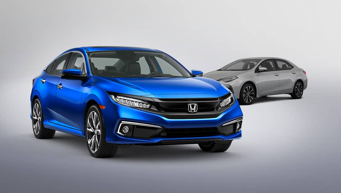 Front 3/4 passenger's side view of 2019 Honda Civic Touring Sedan in Aegean Blue Metallic with competitor vehicle in background.