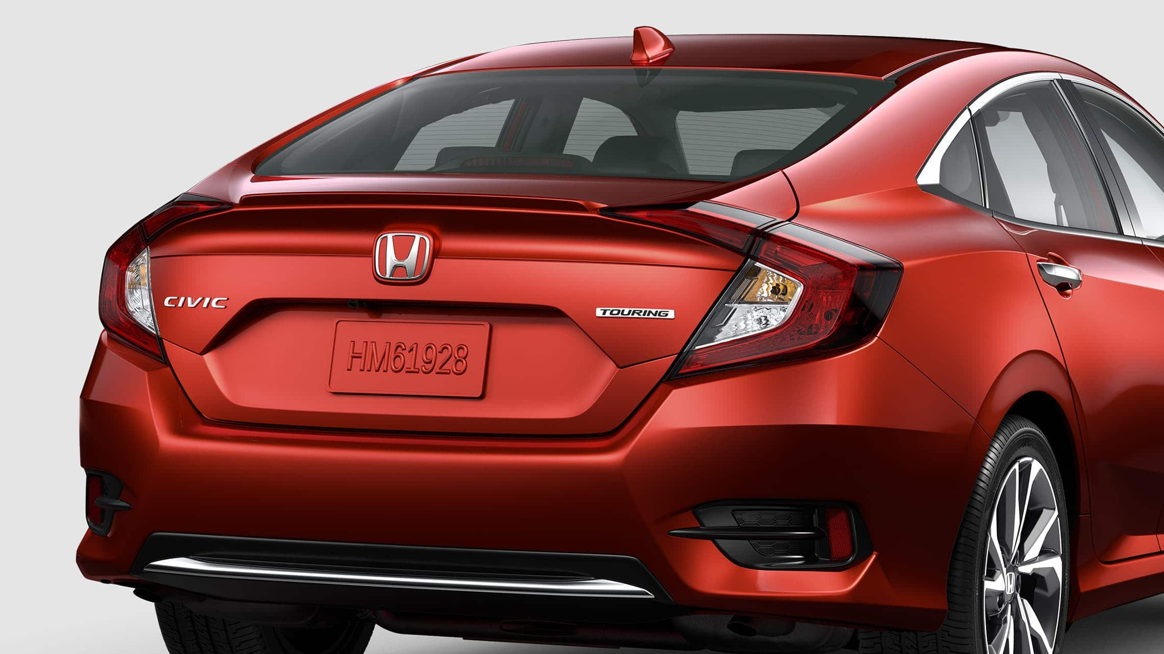Rear passenger-side view of the 2020 Honda Civic Touring Sedan in Molten Lava Pearl.