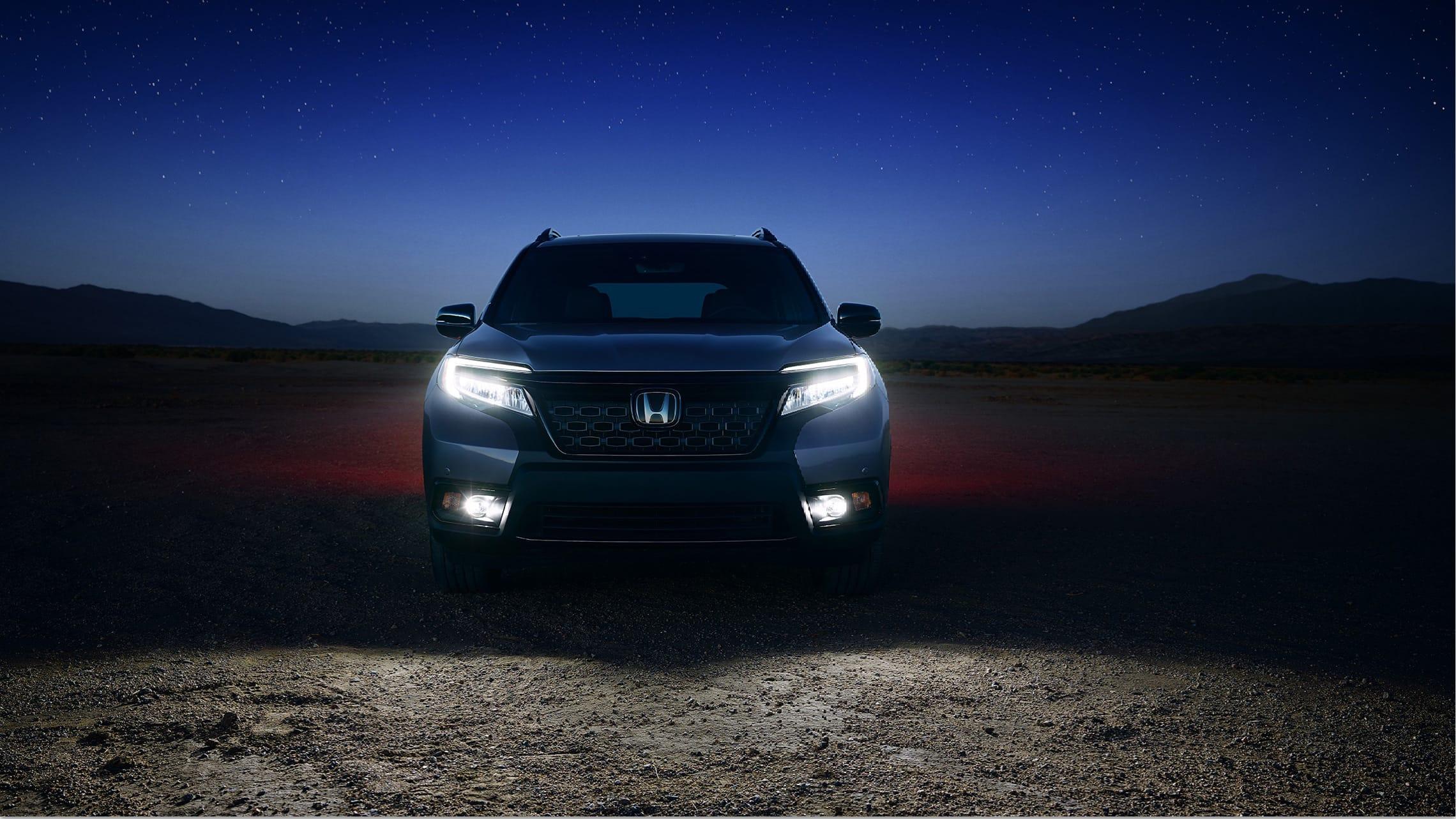 Vista frontal directa de la Honda Passport Elite2021 en Modern Steel Metallic con luces delanteras bajas de LED y faros antiniebla encendidos.
